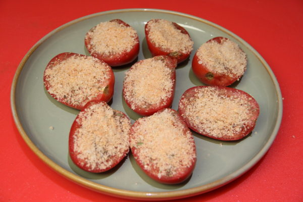Tomato halves that's has a sprinkled Topping mixture over each one.