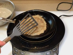 Flipping crepe over with spatula when crepe bottom is light brown color.
