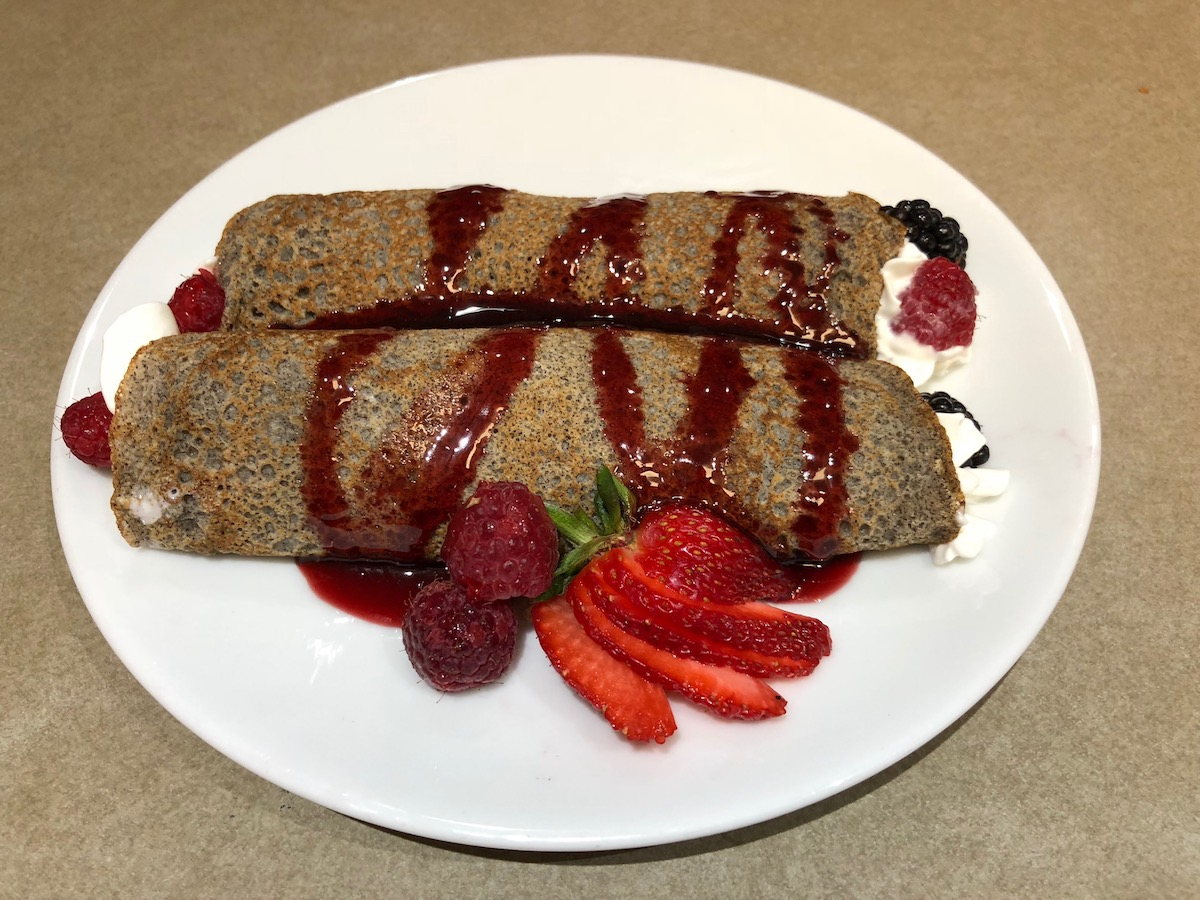 Plated Buckwheat Crepes with Fresh Berries and whipped cream.