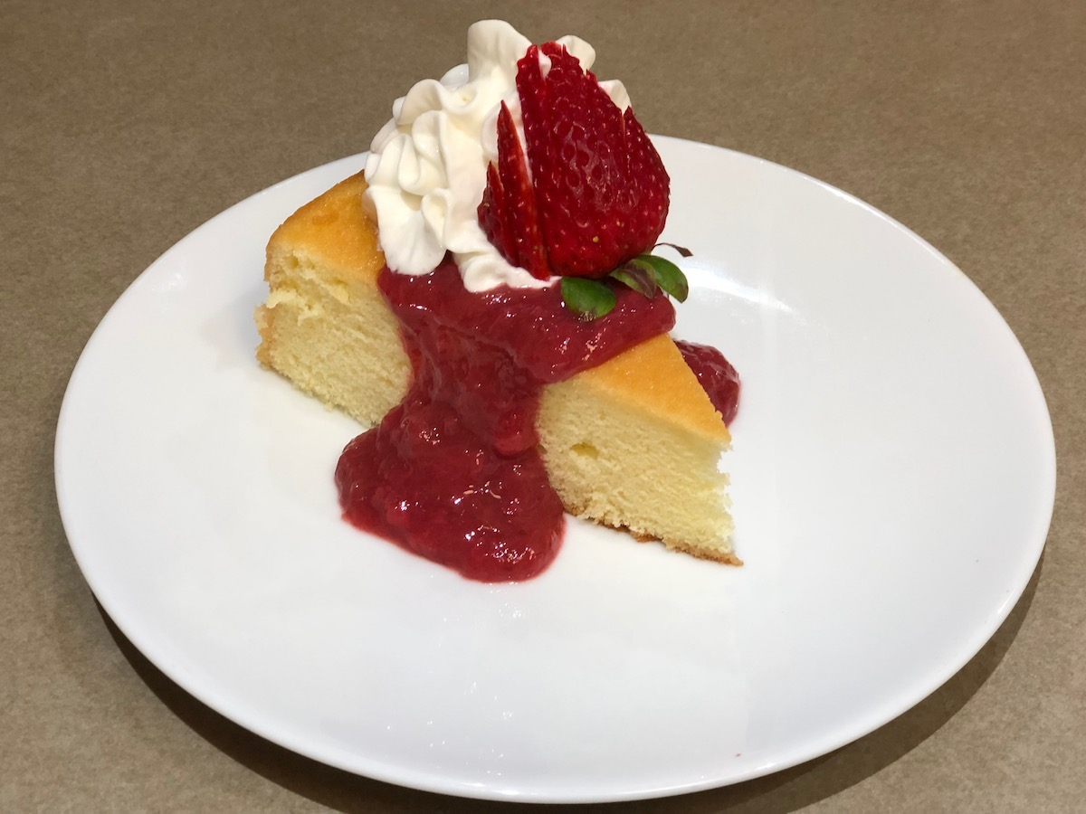 Strawberry Rhubarb Sauce on Lemon Chiffon Cake. Garnished with whipped cream and strawberry fan.