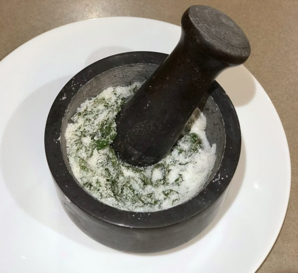 Crushing Chocolate Mint leaves and sugar with Mortar & Pestle.