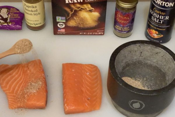 Sprinkling Spicy Seasoning Rub onto salmon filets.