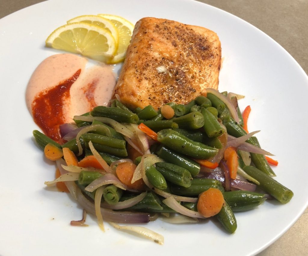 Garnished Spicy Air Fryer Salmon with sautéed green beans mix and Spicy Ranch Dressing